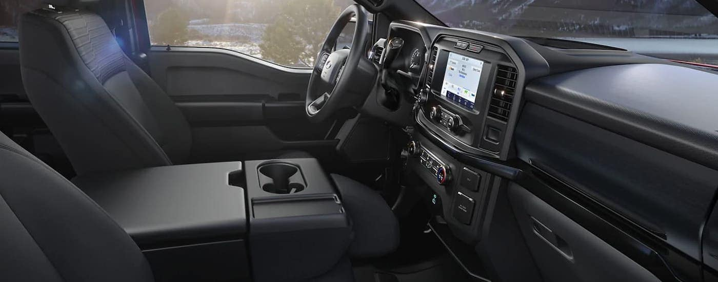 The black interior of a 2021 Ford F-150 is shown from the side.