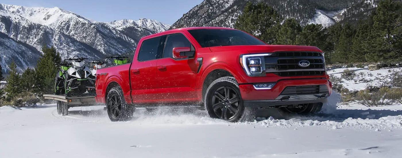 A red 2021 Ford F-150 is towing a trailer in the snow.