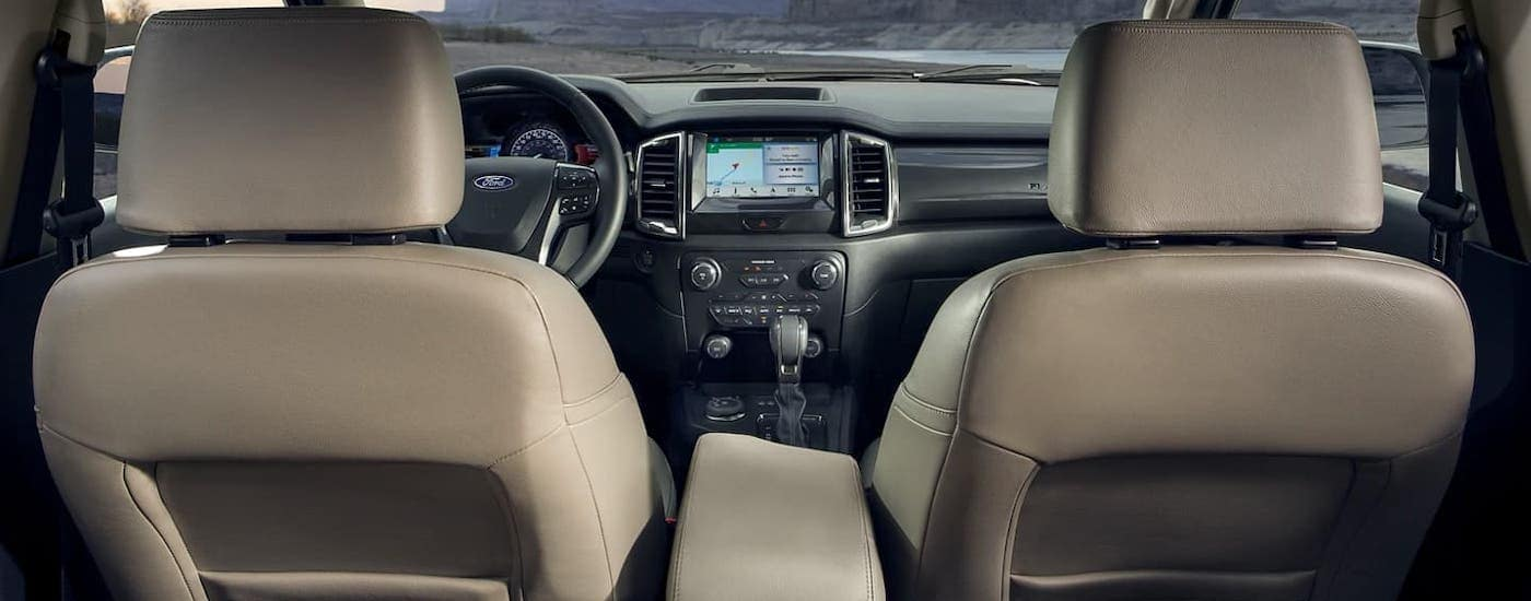 The gray interior of a 2021 Ford Ranger is shown from the rear seat facing the dashboard.