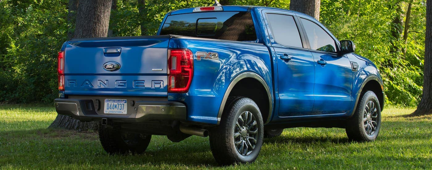 A blue 2021 Ford Ranger FX2 is shown from the rear while parked on grass in front of trees.