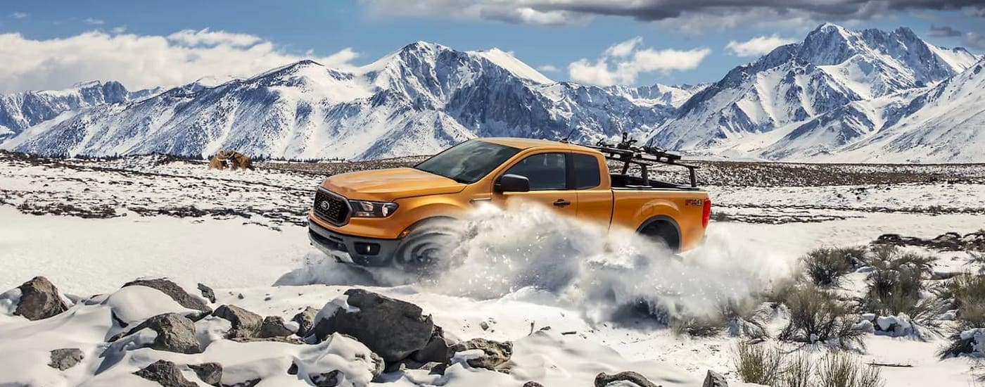An orange 2021 Ford Ranger is driving in the snow in front of distant mountains.