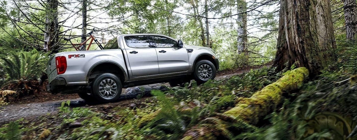 A silver 2021 Ford Ranger is driving through a woodland trail with a bike in the bed.
