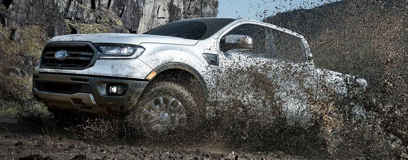 A white 2021 Ford Ranger is kicking up mud after winning the 2021 Ford Ranger vs 2020 Ford Ranger comparison.