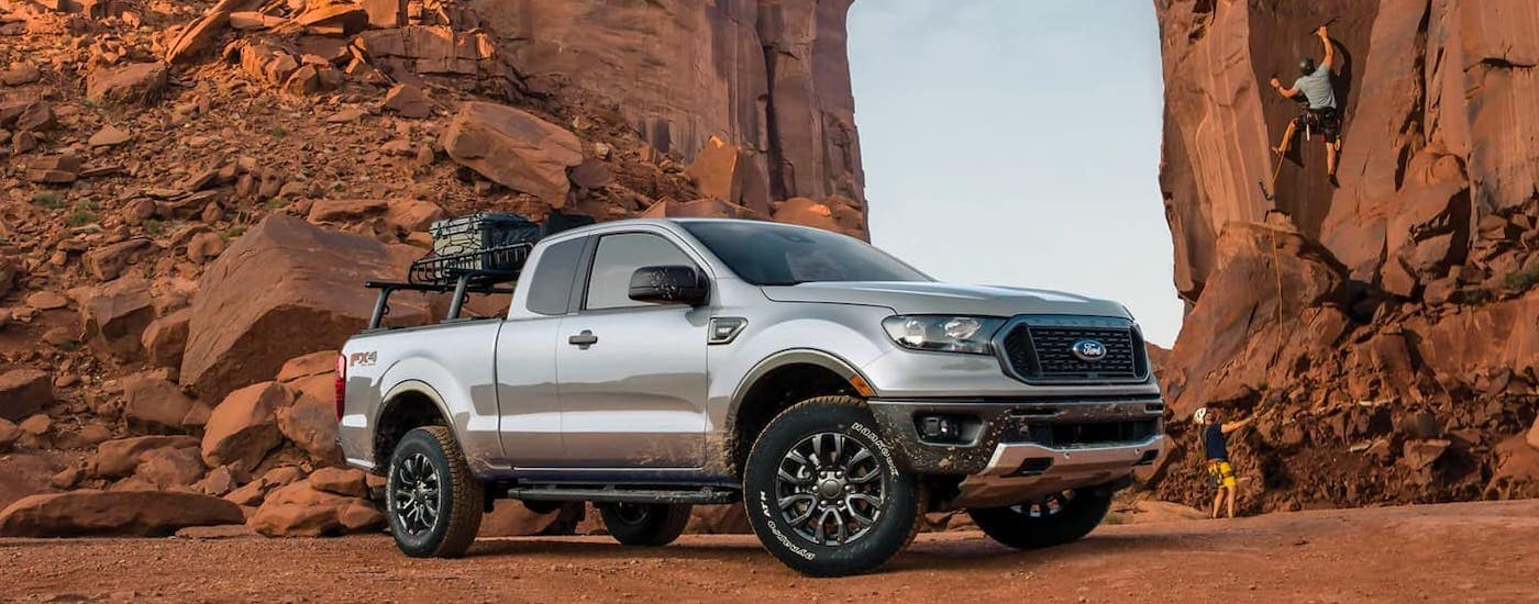 A silver 2021 Ford Ranger is parked in front of cliffs and rock climbers.
