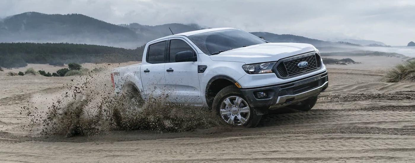 A white 2021 Ford Ranger is kicking up sand after winning the 2021 Ford Ranger vs 2021 Toyota Tacoma comparison.