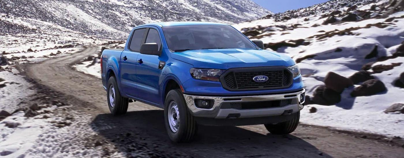 A blue 2021 Ford Ranger is driving on a road through snowy mountains.