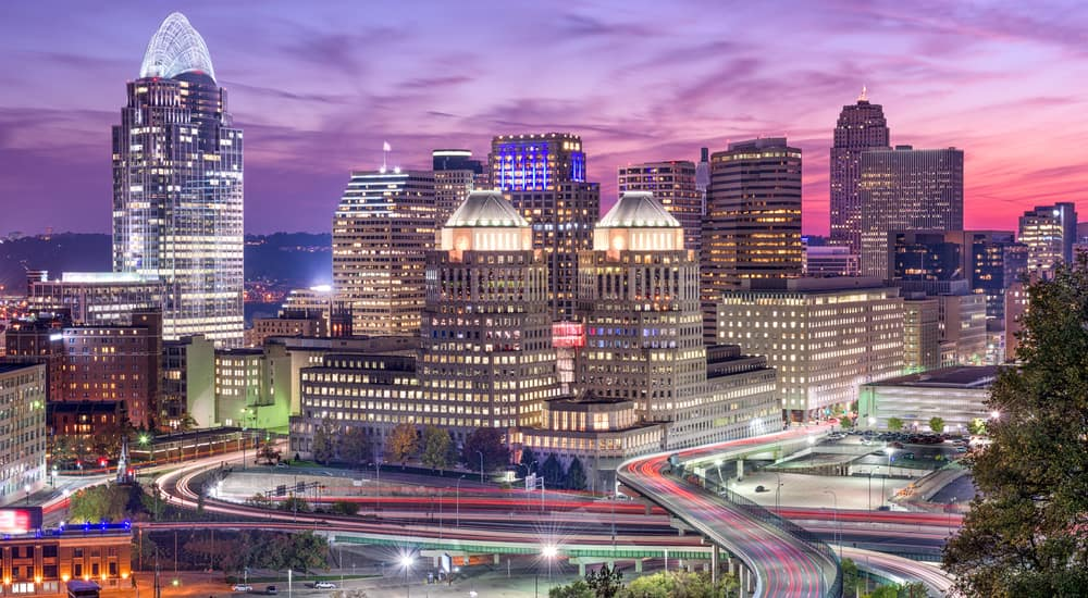 Roads and bridges in front of light up Cincinnati buildings with a purple sky in the background