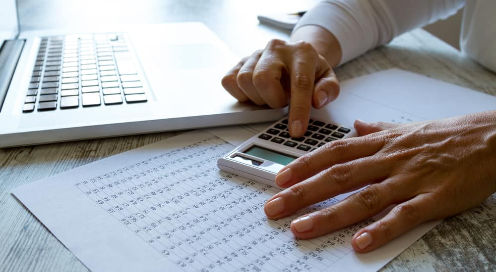 Hands using a calculator on top of a paper and next to a laptop