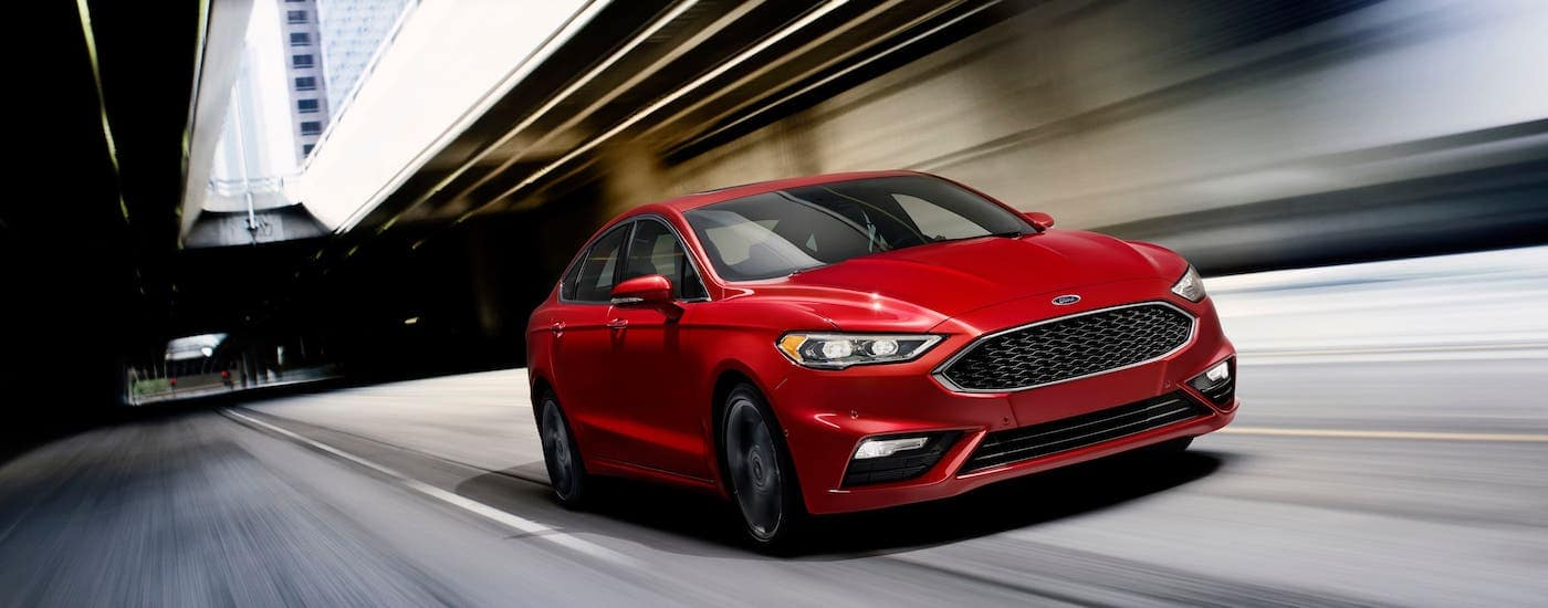 A red 2018 Ford Fusion is driving under a blurry overpass.