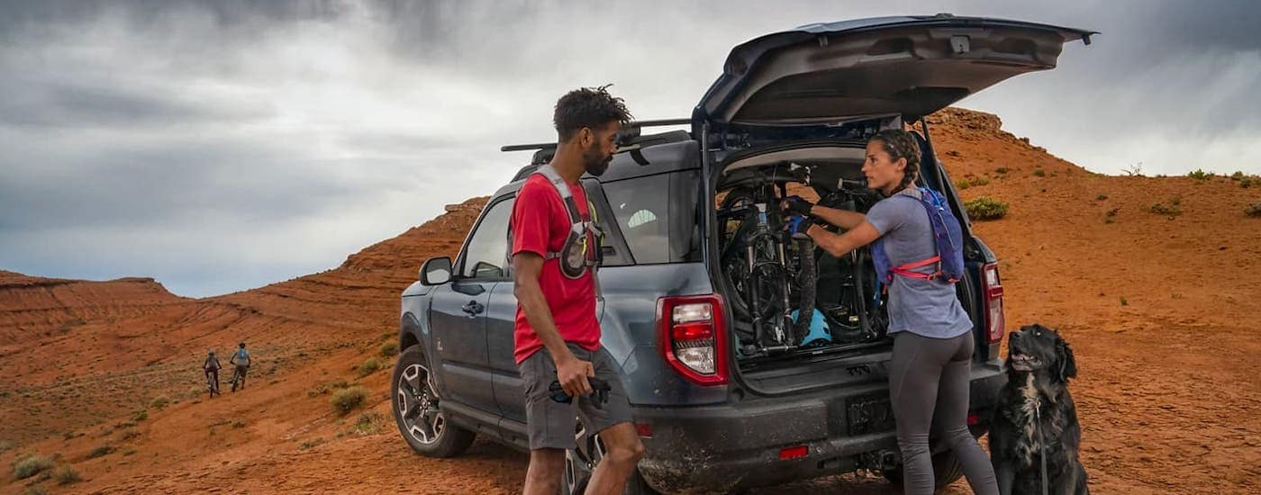 A group of friends are getting bikes out of the cargo area of a gray 2021 Bronco Sport on a sandy trail.