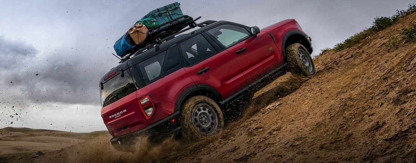 A red 2021 Bronco Sport with luggage on the roof is kicking up sand and climbing a hill after winning the 2021 Bronco Sport vs 2021 Renegade comparison.