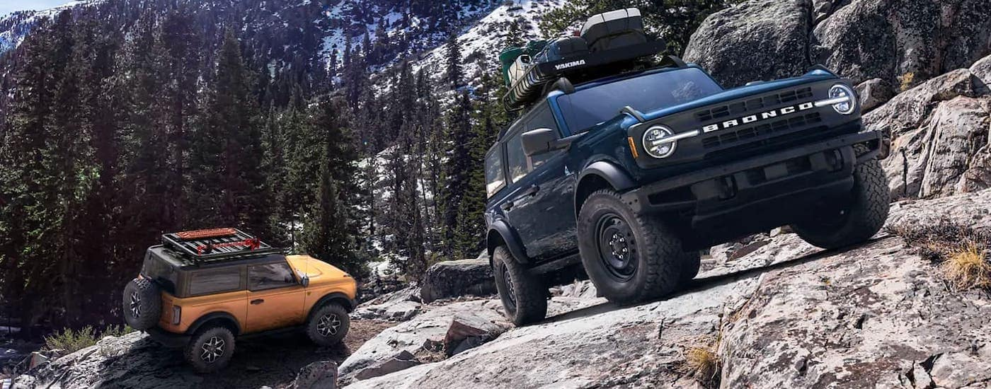 An orange 2021 Ford Bronco 2-door and a blue 4-door are parked on a rocky mountain side after winning the 2021 Ford Bronco vs 2021 Toyota 4Runner comparison.