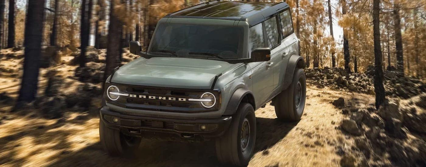 A green 2021 Ford Bronco 4-door Wildtrack is shown from the front while driving on a woodland trail.