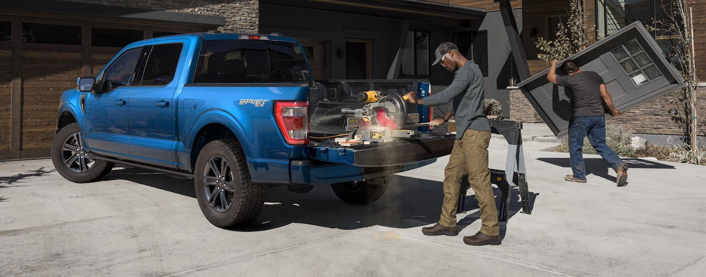 Contractors are working in front of a modern home and in the bed of a blue 2021 Ford F-150.