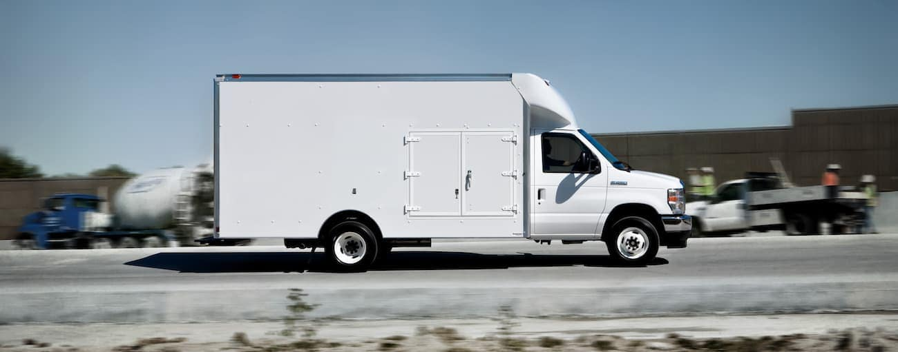 A white 2021 Ford E-Series is shown from the side on a rural road.