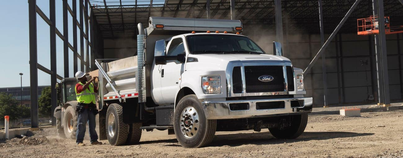 A white 2021 Ford Maximum Duty with a dump body is at a construction site.