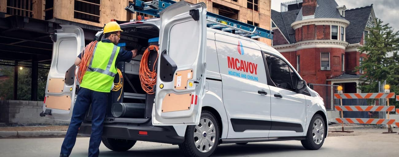 A worker is taking gear out of the back of a 2021 Ford Transit Connect with a logo.