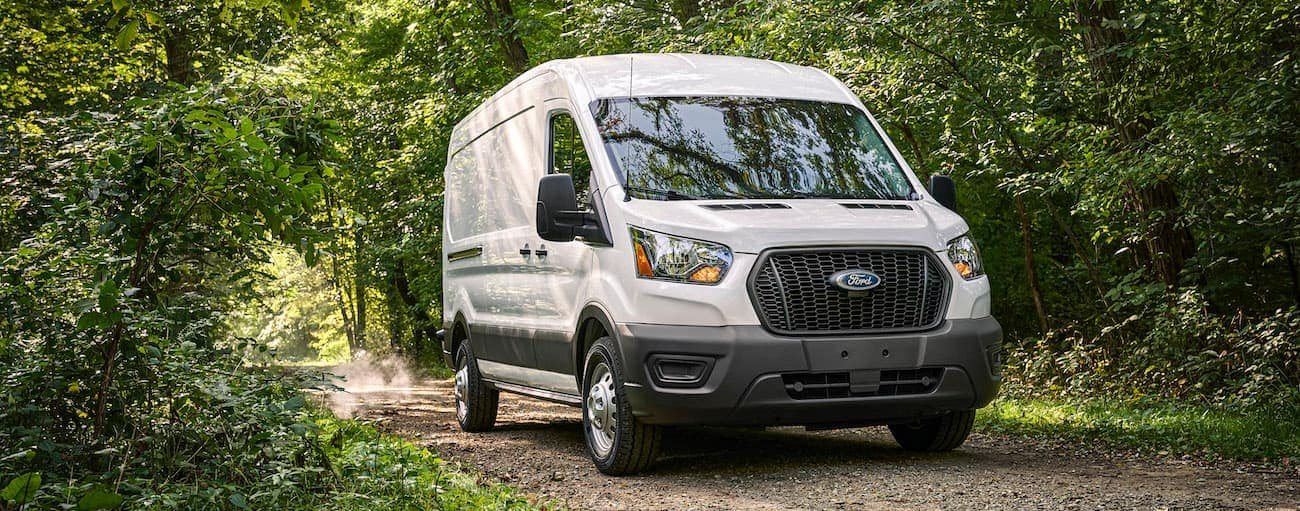 A white 2021 Ford Transit van is driving on a dirt road in the woods.