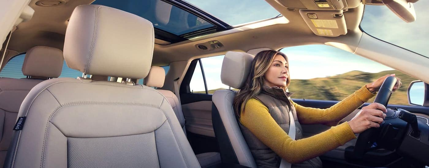 A 2021 Ford Explorer Hybrid is shown with a woman driving in the tan interior.