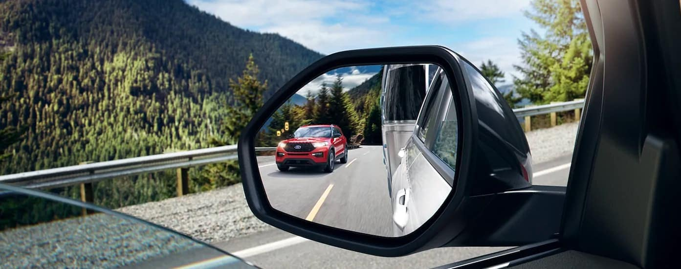 A close up is shown of the mirror and blind spot monitoring icon on a 2021 Ford Explorer Hybrid.