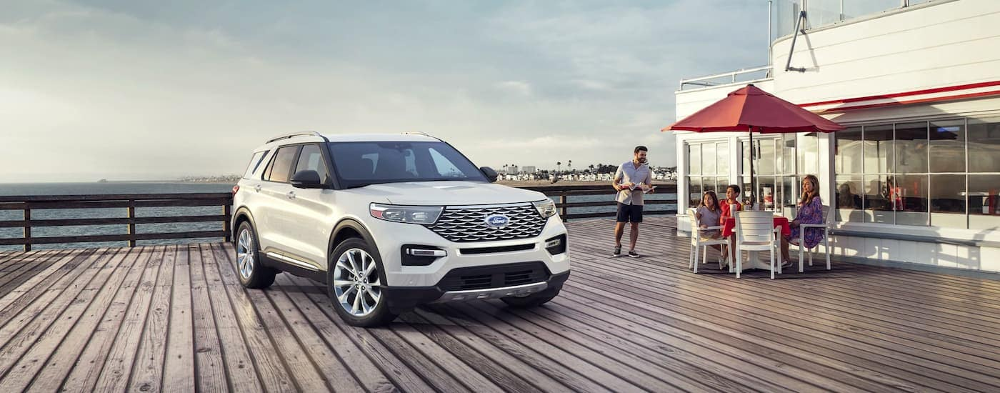 A white 2021 Ford Explorer Hybrid is shown parked next to a family eating on the pier.