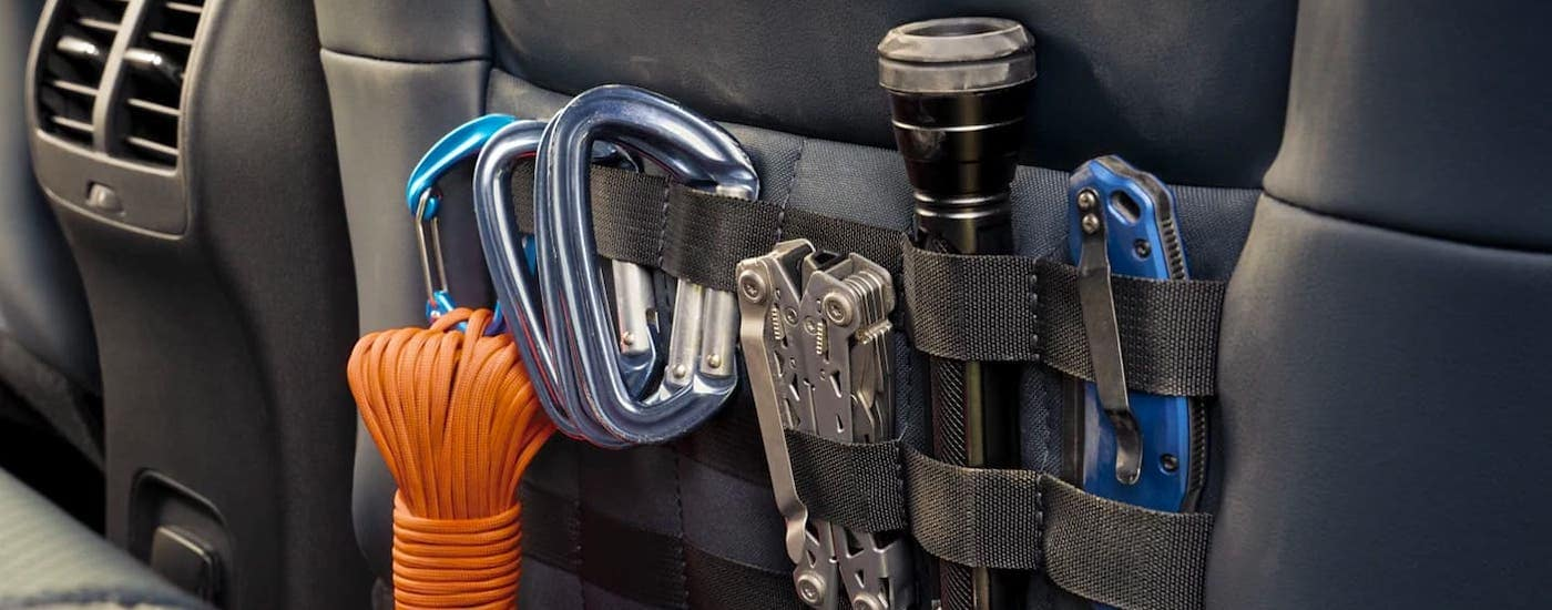 A closeup shows climbing and camping equipment stored in the MOLLE straps on the back of the front seats in a 2021 Bronco Sport.