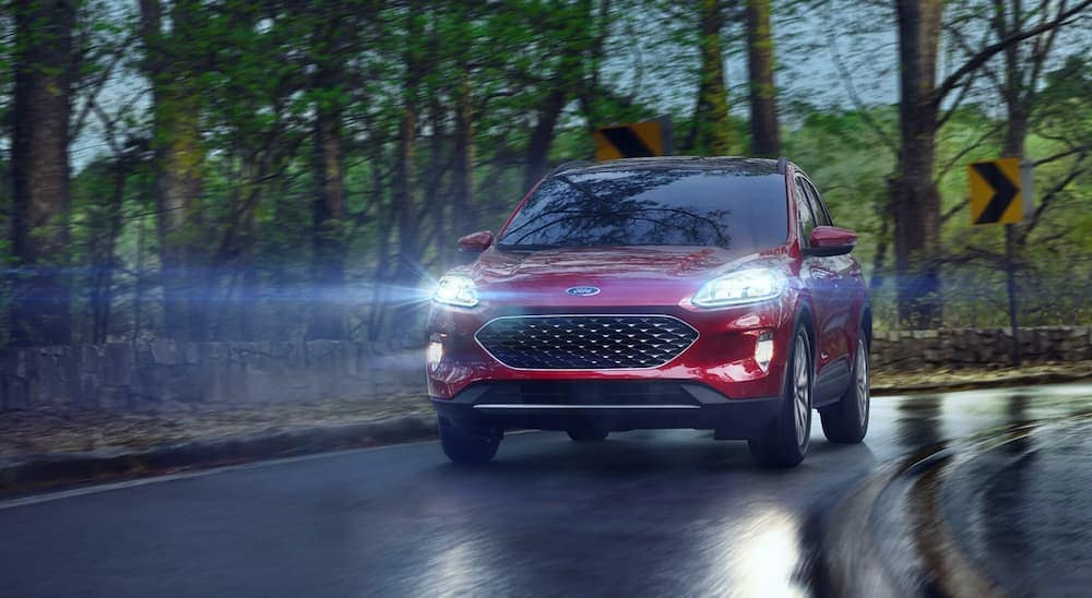A red 2021 Ford Escape Hybrid is shown driving down a wet road with its headlights on.