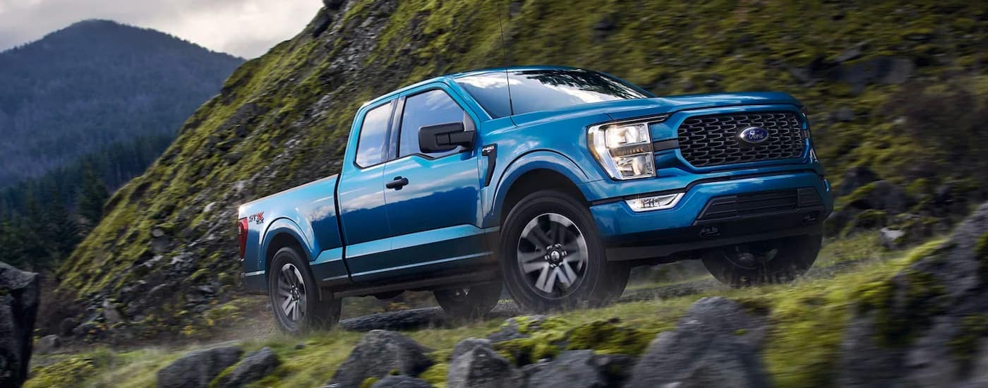 A blue 2021 Ford F-150 Hybrid is shown driving up a steep road in the mountains past mossy rocks.