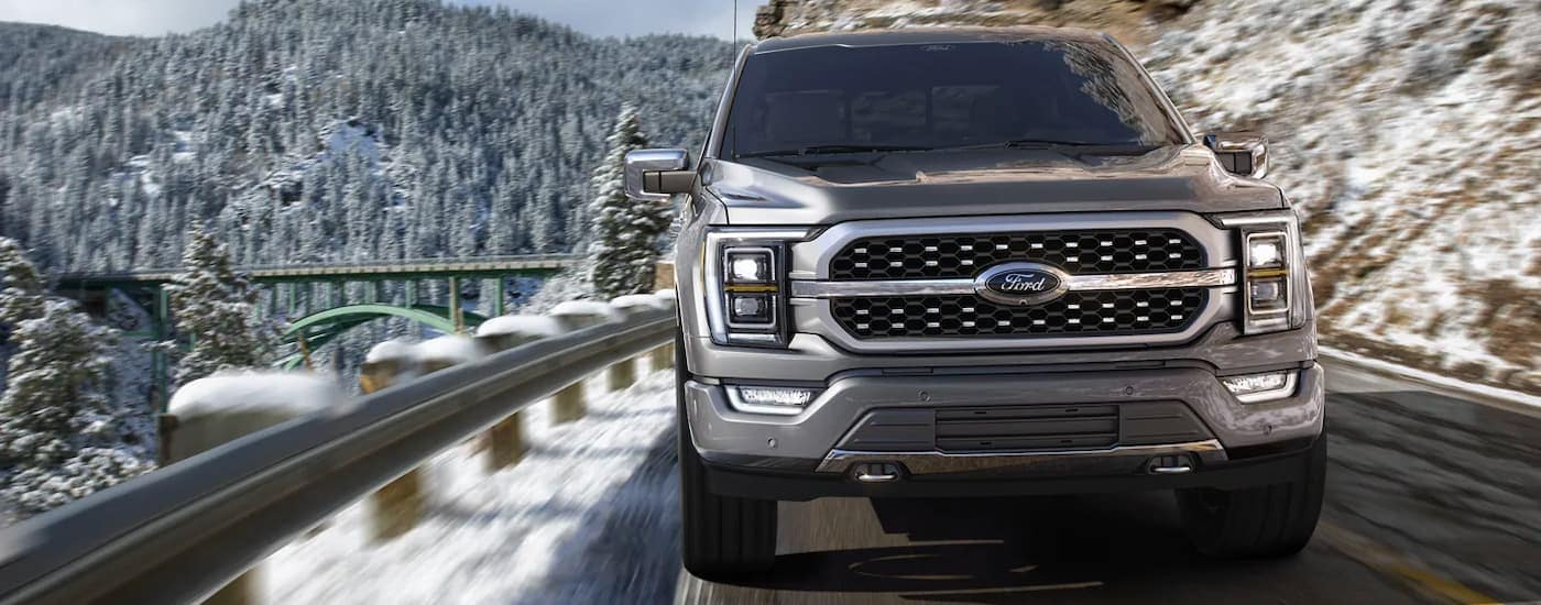 A silver 2021 Ford F-150 Hybrid is shown from the front driving through snowy mountains.