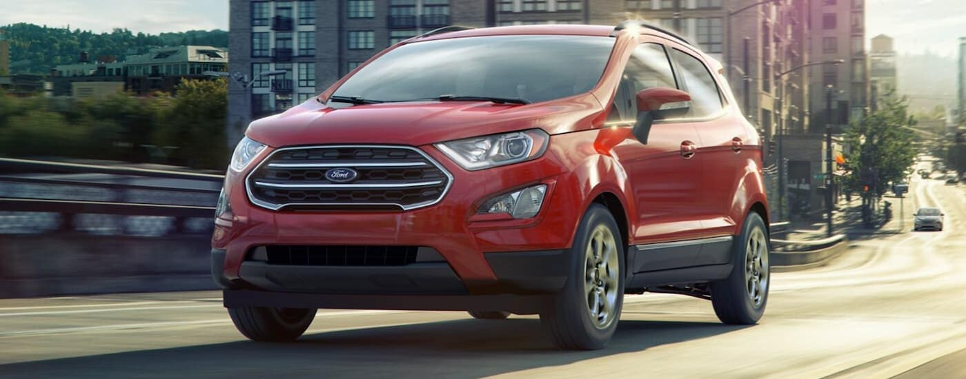 A red 2021 Ford EcoSport is diving on a city street.