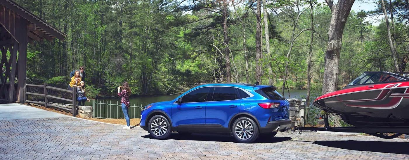 A blue 2021 Ford Escape is shown from the side with a boat on a trailer and a family taking photos.