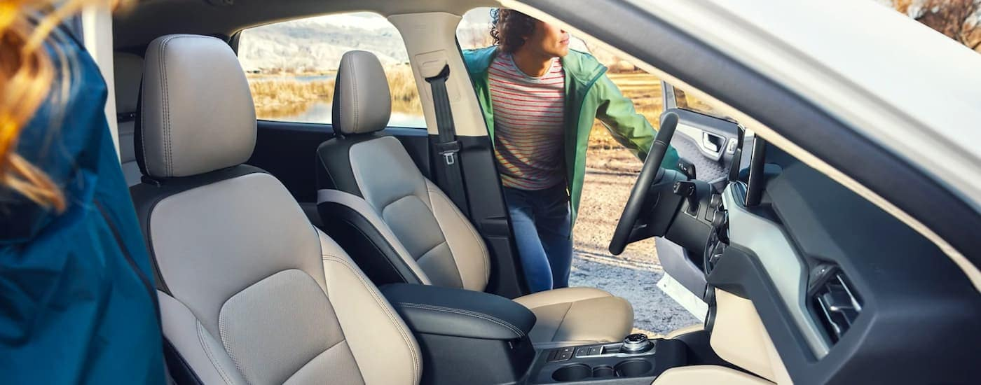 The black and grey interior is shown on a 2021 Ford Escape with a people getting in the front seats.