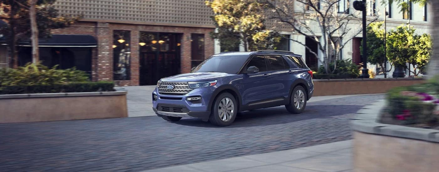 A pale blue 2021 Ford Explorer is shown driving past blurred brick buildings.