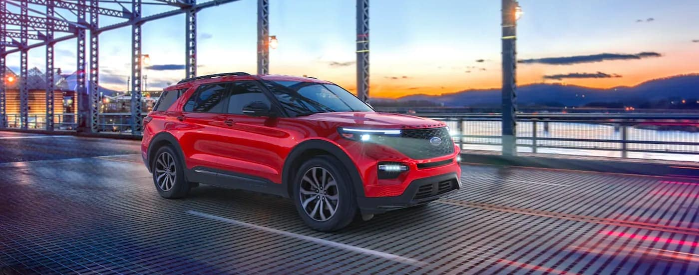 A red 2021 Ford Explorer is shown from the side driving over a metal bridge.