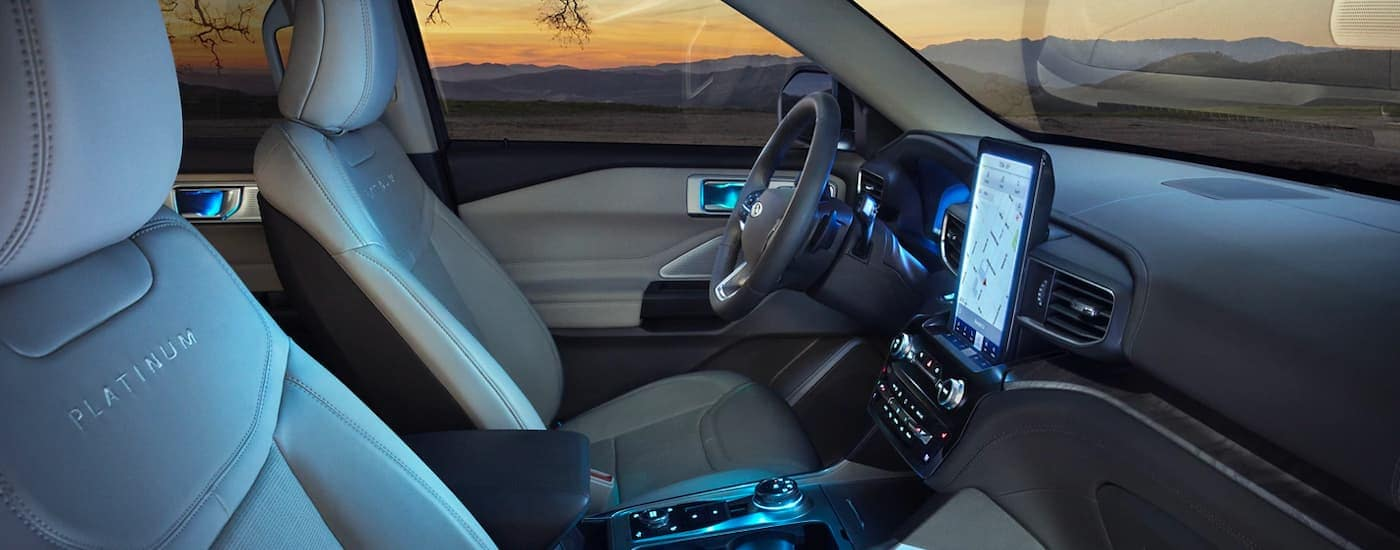 The interior and illuminated infotainment screen is shown from the passenger side on a 2021 Ford Explorer.