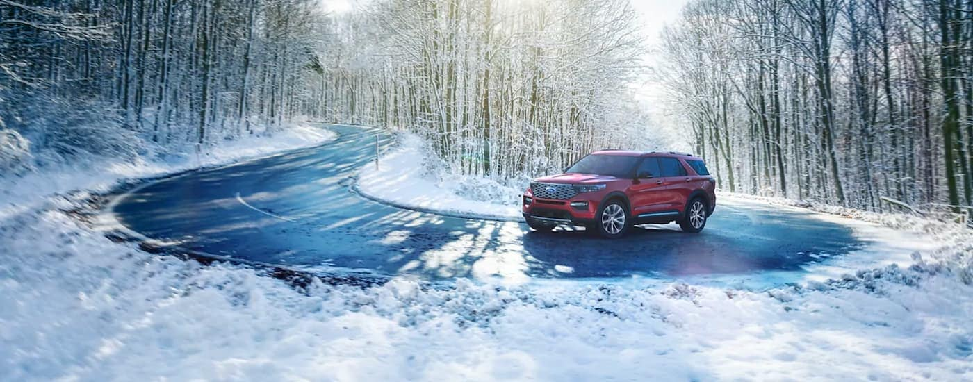 A red 2021 Ford Explorer is rounding the corner on a snowy tree-lined road.