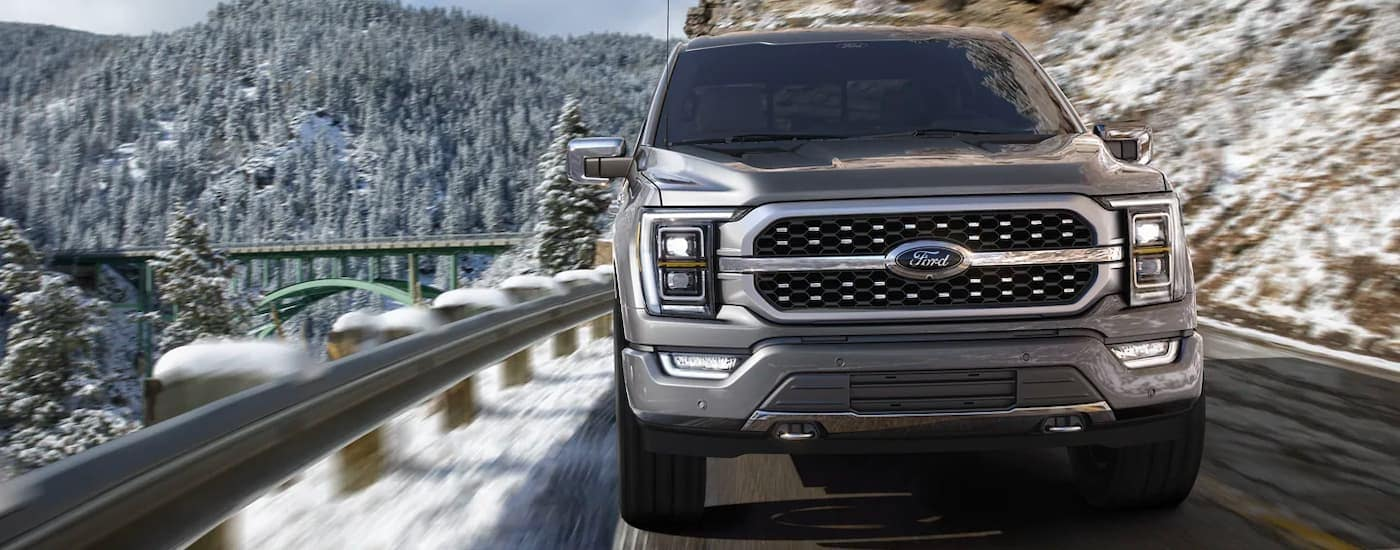 A silver 2021 Ford F-150 is shown from the front driving down a snowy mountain road with a bridge in the background.