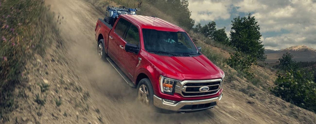 A red 2021 Ford F-150 is speeding down a hill after winning the 2021 Ford F-150 vs 2021 Ram 1500 face-off.