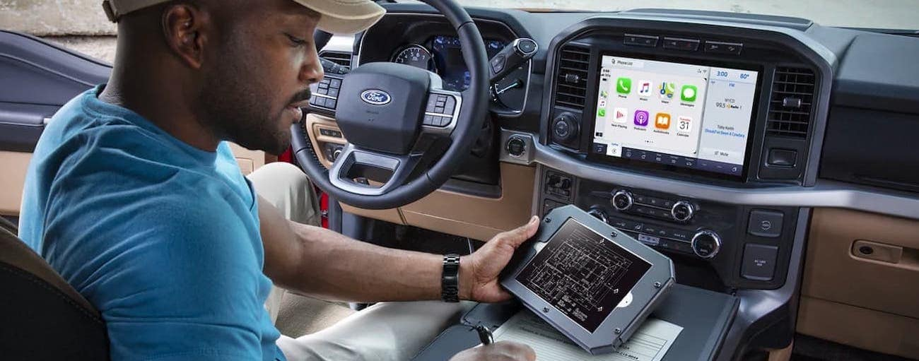 A close up shows a man looking at blueprints on a tablet while sitting in a 2021 Ford F-150.
