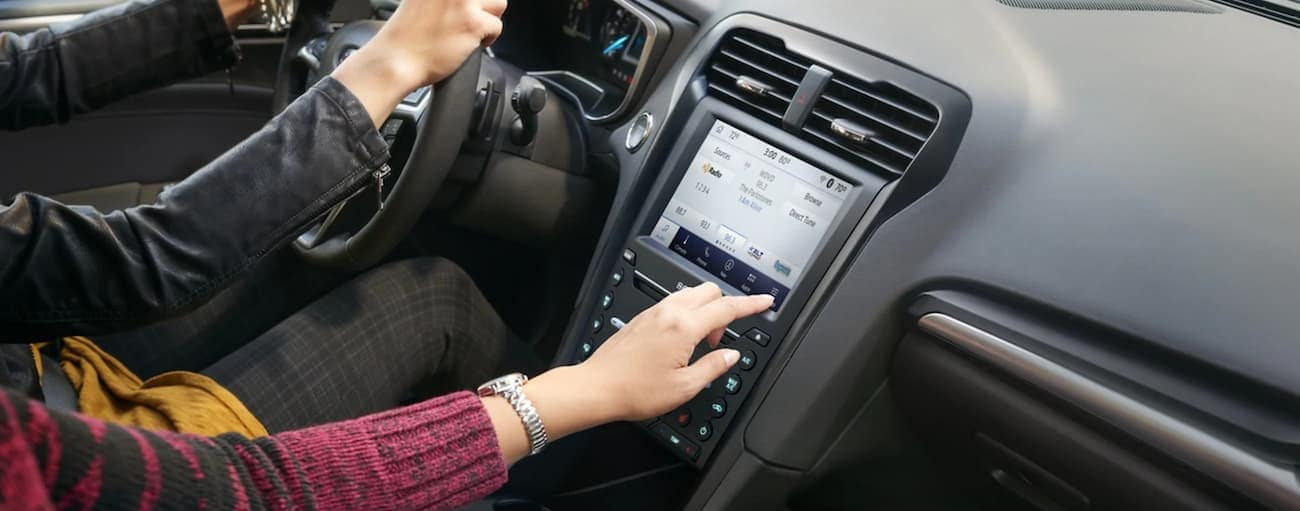 A passenger is using the touch screen in a 2020 Ford Fusion.