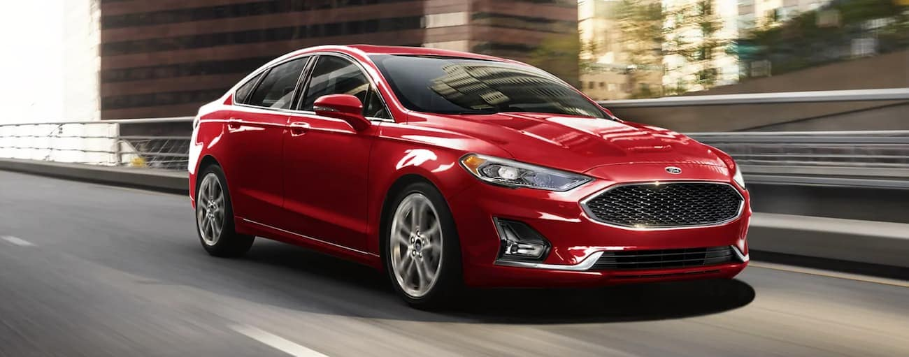 A red 2020 Ford Fusion is driving on a highway past city buildings after winning the 2020 Ford Fusion vs 2021 Toyota Camry comparison.