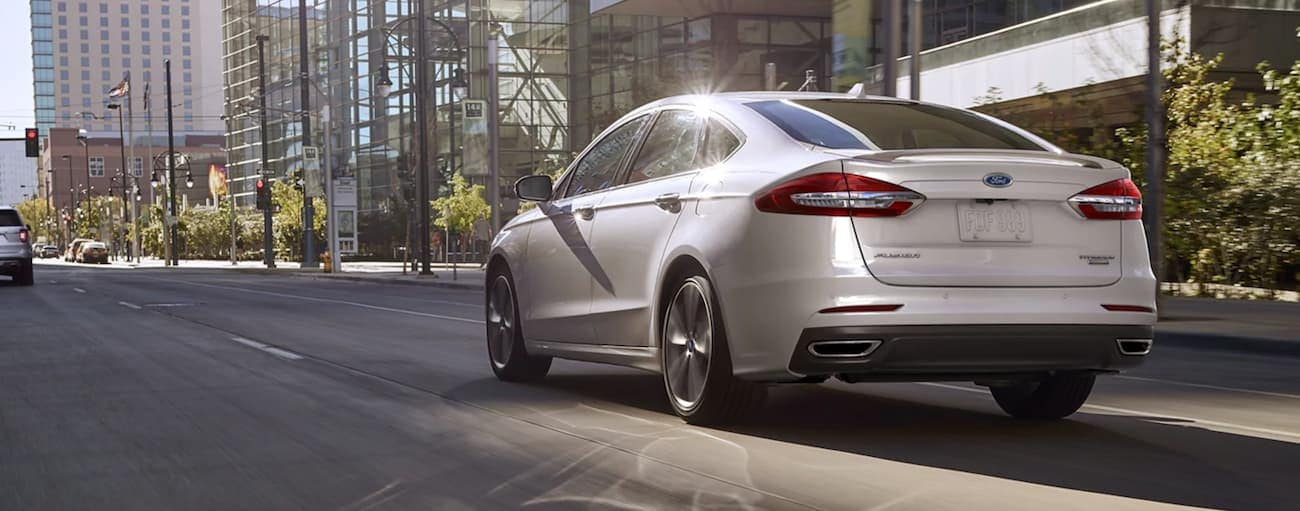 A white 2020 Ford Fusion is shown from the rear on a city street with multiple lanes.