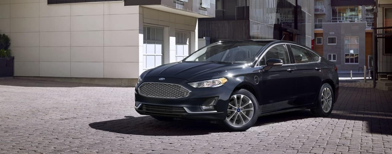 A black 2020 Ford Fusion is parked on pavers in front of town houses.