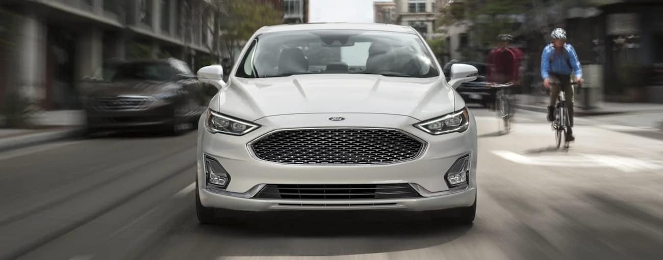 A white 2020 Ford Fusion is shown from the front on a city street after winning the 2020 Ford Fusion vs 2021 Nissan Altima comparison.