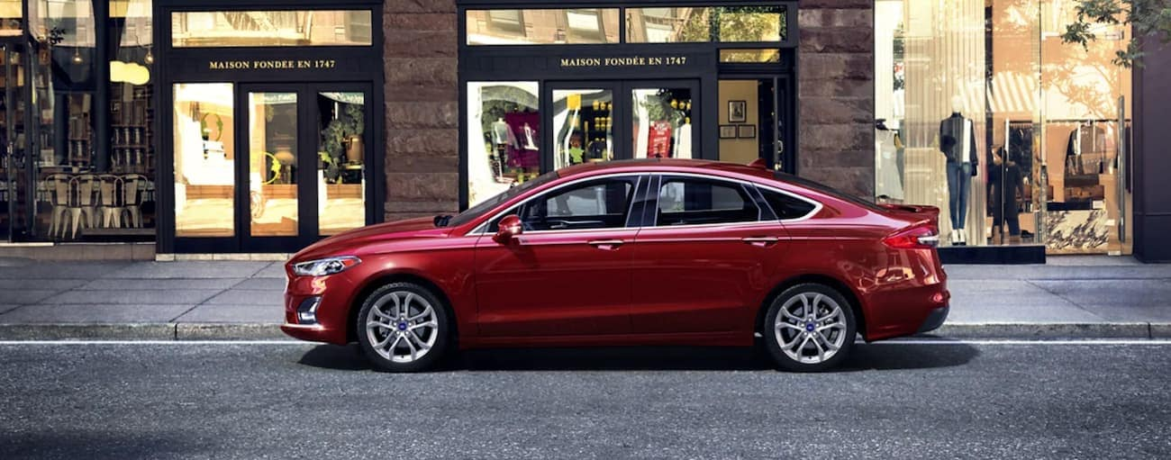 A red 2020 Ford Fusion is parked in front of a brick building.