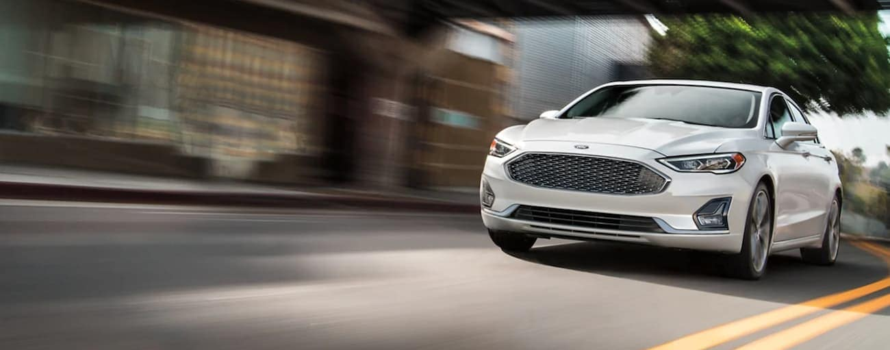 A white 2020 Ford Fusion is driving on a city street after winning the 2020 Ford Fusion vs 2021 Toyota Camry comparison.