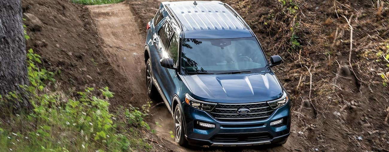 A blue 2021 Ford Explorer is shown from a high angle on a dirt road during the 2021 Ford Explorer vs 2021 Ford Bronco comparison.