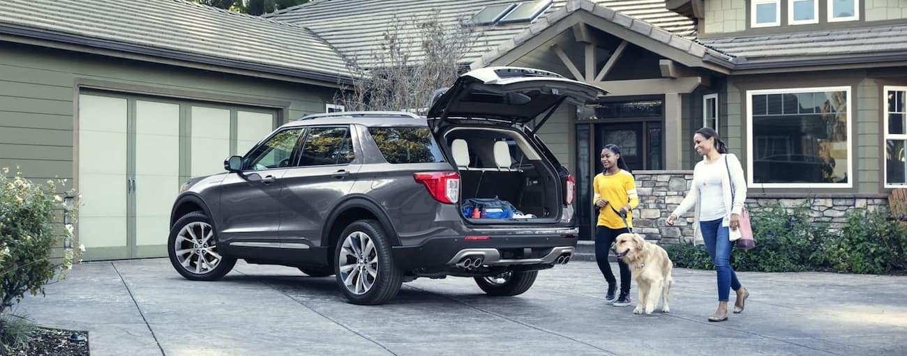 A mother, daughter, and dog are at the back of a grey 2021 Ford Explorer with an open trunk in a driveway.