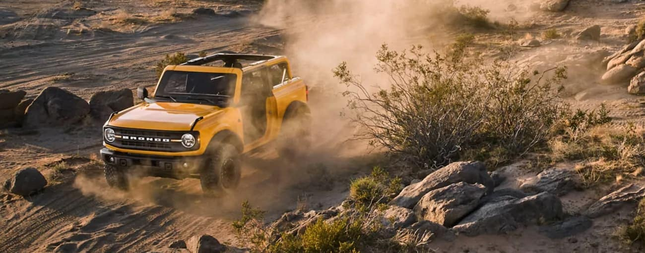 A yellow 2021 Ford Bronco Two Door is kicking up dust while off-roading on a desert trail.