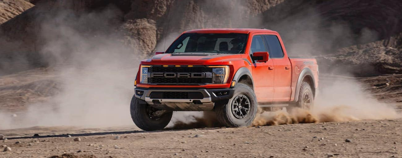 A red 2021 Ford F-150 Raptor is off-roading on dirt after winning the 2021 Ford F-150 Raptor vs 2021 Ram 1500 TRX comparison.